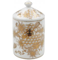 A golden trimmed candle pot decorated with a luxe Honeycomb design