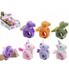 An assortment of plush unicorns and dragons and on a huggler bracelet.