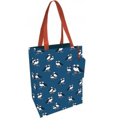 A sleek gift bag decorated with a puffin print on a navy background