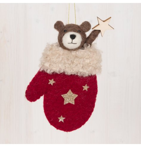 A festive little woollen bear hanging decoration popping out of a red mitten holding a star