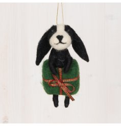 A sweet and small woollen hanging dog popping out of a present