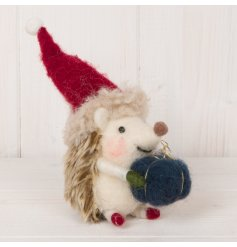 An adorable woollen hedgehog decoration complete with a navy blue parcel and festive hat