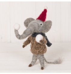 An adorable woollen elephant decoration dressed up and holding snowballs