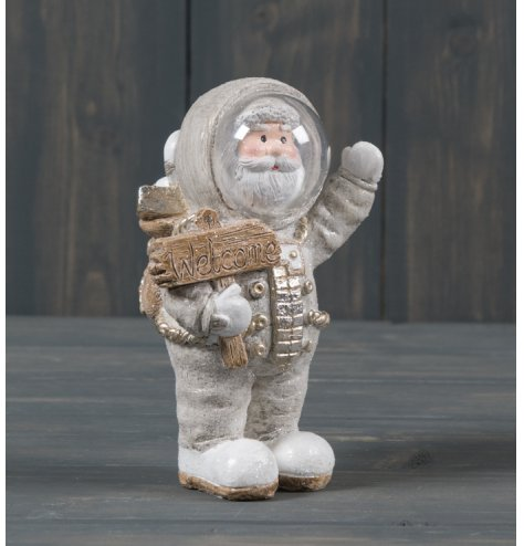A small ceramic Santa dressed up as an astronaut, complete with gold trimmings and a sprinkle of glitter