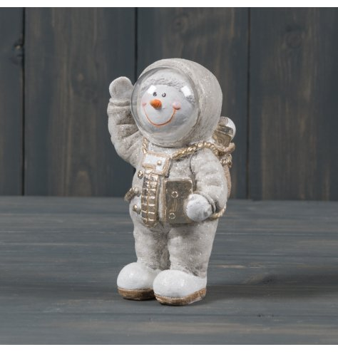 A small ceramic snowman dressed up as an astronaut, complete with gold trimmings and a sprinkle of glitter