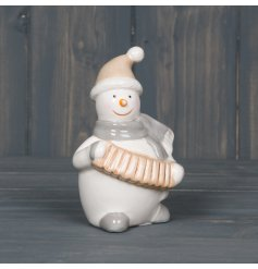 A sweet little smooth ceramic snowman playing an accordion