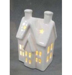 A warm glowing LED Ceramic House with added cut windows and stars