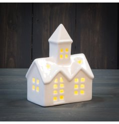 A warm glowing LED Ceramic Church with added cut windows and stars