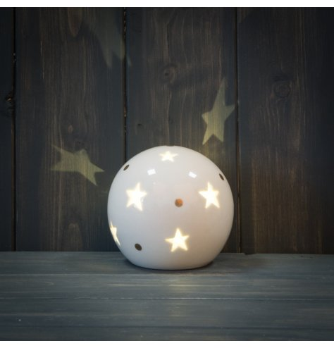 A smooth ceramic ball ornament with a star cut decal and warm glowing LED centre