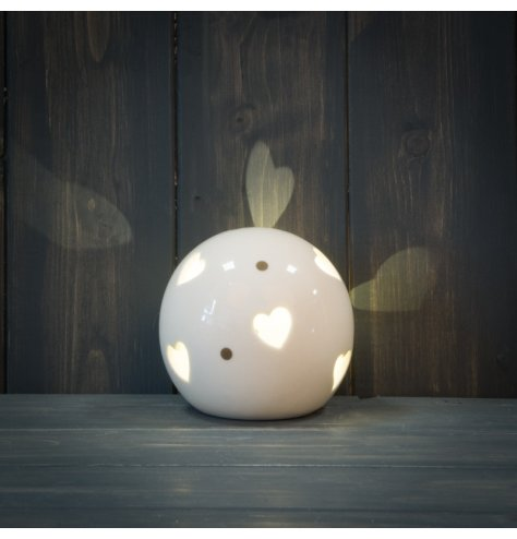 A smooth ceramic ball ornament with a heart cut decal and warm glowing LED centre