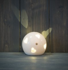 A small and simple rounded ceramic ball set with heart cut details and added gold dots