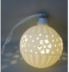 A small white ceramic bauble with a warm glowing LED centre