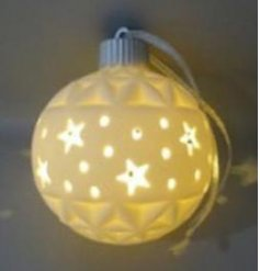 A charmingly simple white ceramic bauble with a star cut decal and warm glowing LED centre