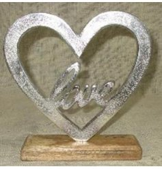 Set with a natural wooden block base, this decorative aluminium heart also features a scripted text centre
