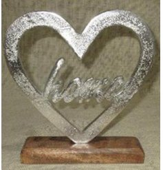 Set with a natural wooden block base, this decorative aluminimum heart also features a scripted text centre