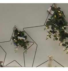 A large black wire Star complete with a eucalyptus foliage and warm glowing LED lights