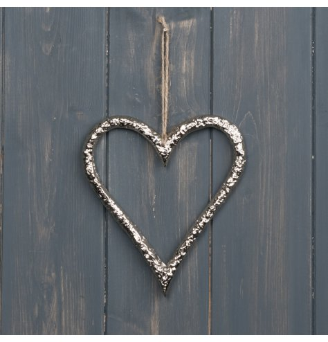 A hammered metal heart with a sleek silver tone and jute string hanger