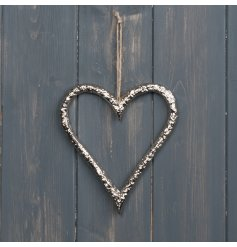 A rough silver coated metal heart decoration with a string hanger