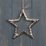 A rough silver coated metal star decoration with a string hanger