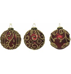 An assortment of mercury splash ox-blood red glass baubles, each beautifully decorated with a golden bead design