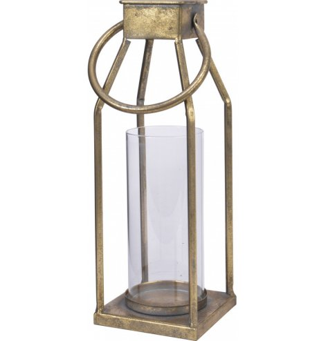 A simplistic decorative metal lantern set with a glass insert and tarnished gold tone