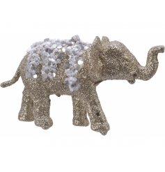A hanging decorative elephant covered in a golden glitter and finished with a bead and sequin design