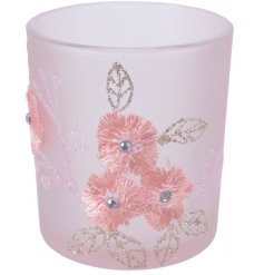 A pretty pastel pink glass tlight holder decorated with a delicate embroidery inspired design and added glittery accent