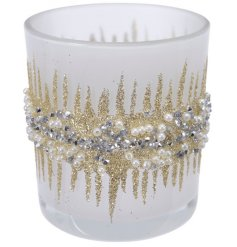 Perfect for adding a glittery touch to any home space, a glitter covered tlight holder with a frosted coating to it