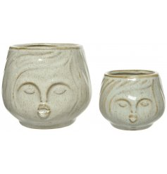 Sure to add a charming touch to any home space, an assorted sized set of stoneware vases with facial details