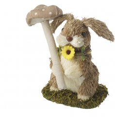 A natural straw rabbit sheltering beneath a mushroom with a little daisy.