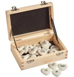 A box containing a variety of small marble heart tokens, each printed with its own text and illustration
