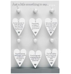 A large assortment of hanging white heart signs each decorated with a sweetly scripted text decal