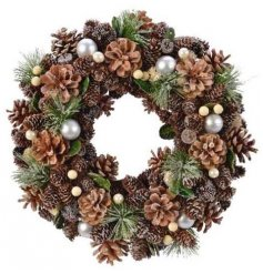 A beautiful round wreath made up of woodland foliage, pinecones, berries and baubles