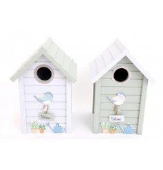 Assorted by their sage green and white tones, a mix of cutely decorated wooden bird houses