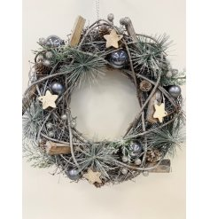 A decorative pine wreath with added glittery accents and wooden touches surrounded by a woven wicker decal