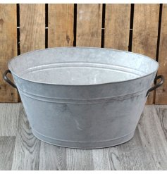 a large oval shaped zinc planter with added metal handles and a whitewash tarni