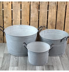 A set of assorted sized distressed zinc planters with added metal handles and a rough white wash finish to each