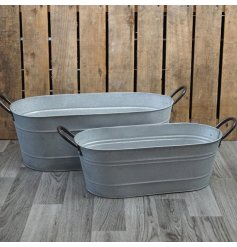 A set of 2 aged zinc troughs with black handles.
