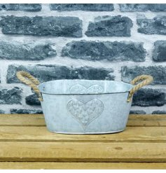 A rustic zinc planter with an embossed heart design and twin chunky rope carry handles.