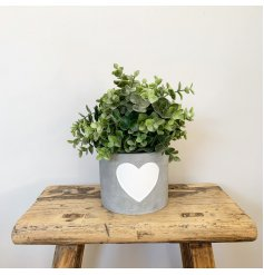 A stylish cement pot with a white painted heart decoration. Ideal for planting and candles.