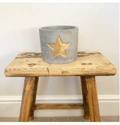 A rustic cement planter with a gold painted star. A chic interior accessory which can also be used as a t-light holder
