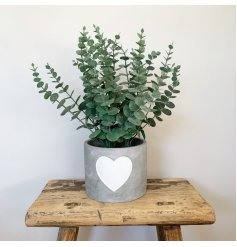A rough luxe cement planter with a white painted heart. A chic decorative item for the home.