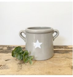 A chic grey pot with ears. Decorated with a simple white star design.