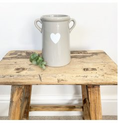 A stylish pot with twin ears and a pretty white heart decoration.