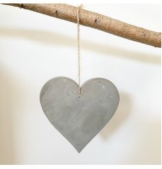 A rustic cement heart decoration with a jute string hanger.
