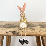 A wonderfully detailed sitting rabbit decoration, complete with a Santa hat, boots and gold star.