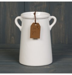 A sleek and simplistic tall ceramic vase with added tapered ear handles and a faux leather tag