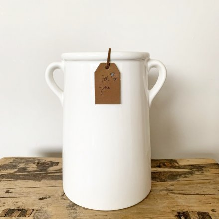 A classic white ceramic vase with small eared handles. A timeless home accessory, complete with a stylish tag.
