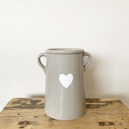 A chic and simple ceramic vase with a white heart shaped decal. Complete with small twin handles.