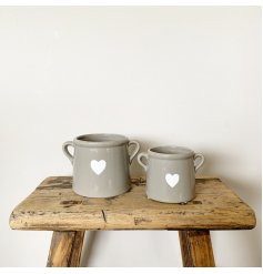 A beautiful ceramic pot with a chic white heart decal. Complete with small handles.